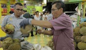 Zainal Abidin (baju merah) alias Ucok pemilik usaha Durian Ucok di Kota Medan sedang memilihkan durian pesanan para pelanggan. MTD/kompas.com/roderick adrian mozes