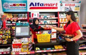 Seorang karyawan toko melayani konsumen yang melakukan proses pembayaran usai berbelanja di Alfamart. (sumber:internet)