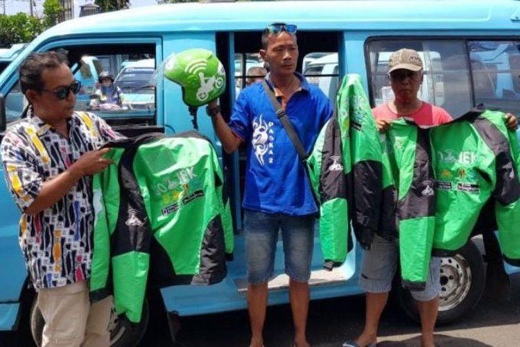 Awak angkot Salatiga menunjukkan helm dan jaket yang disita dari pengemudi Go-Jek, Senin (4/9/2017). (Tribun Jateng/Deni Setiawan)