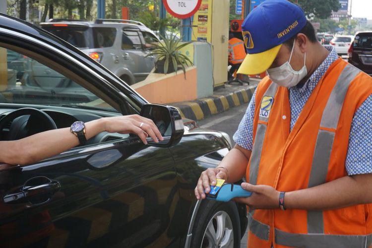 Petugas GT Toll pasteur tengah melayani pengemudi yang hendak masuk ke GT Tol Pasteur, di Bandung, Senin (25/12/2017) dengan alat pembaca uang elektronik portabel.(KOMPAS.com/AGIEPERMADI)