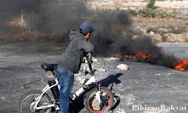Seorang anak menyaksikan sisa demonstrasi terhadap Donald Trump di Ramallah beberapa waktu lalu.