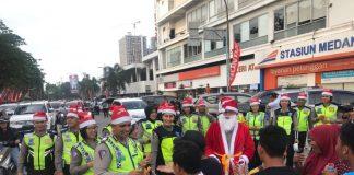 Kasat Lantas Polrestabes Medan, AKBP Muhammad Saleh memberikan hadiah kepada warga yang melintas di seputaran Lapangan Merdeka. Hal ini dilakukan untuk menyambut Natal dan Tahun Baru 2018, Sabtu (23/12/2017)