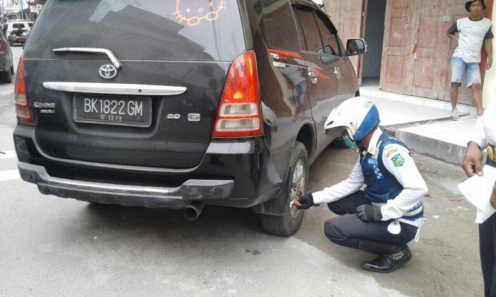 Penggembosan kendaraan oleh pihak Dishub Kota Medan bersama Satlantas Polrestabes Medan di Jalan Balai Kota, Medan, Kamis (4/1/2018). (Mtd/Siti Suhaima)
